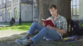 Young man reading book with fascinating storyline, empathizing with characters. Stock footage stock video footage