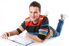 Young man reading a book on the floor isolated Royalty Free Stock Photography