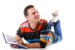 Young man reading a book on the floor isolated Stock Images