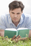 Young man reading book on grass against sky Stock Photos