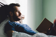 Young man reading a book in his bedroom. Young bearded man reading a book in his bedroom Royalty Free Stock Photography