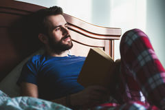 Young man reading a book in his bedroom. Looking to the window Royalty Free Stock Images