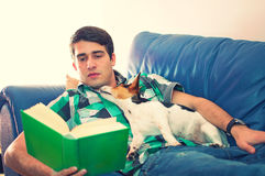 Young man reading a book with his dog on a couch. Portrait of an attractive young man with the book and his cute dog on couch in his living room over white Royalty Free Stock Photo
