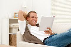 Young man reading a book at home Royalty Free Stock Images