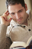 Young man reading book at home Royalty Free Stock Photography