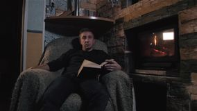 Young Man Reading Book at Home Near Fireplace At Home, Holiday And Lifestyle Concept stock video