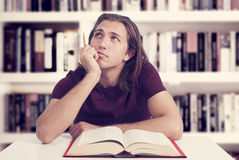 Young man reading book in library Royalty Free Stock Photos