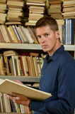 Young man reading a book in the library Stock Photo