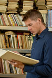 Young man reading a book in the library Stock Photography