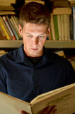 Young man reading a book in the library Stock Photos