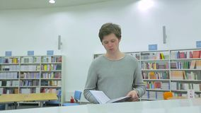 Young Man Reading Book in Library. Student Reading Book in Library stock footage