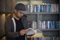 Young man reading book in library. Student in college study from book, knowledge in university concept. Study hard for exam. People, knowledge, education and royalty free stock photography