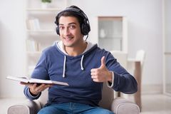 The young man reading book and listening to audio book Stock Images