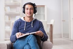The young man reading book and listening to audio book. Young man reading book and listening to audio book Stock Photography