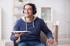 The young man reading book and listening to audio book Stock Photography