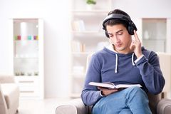 The young man reading book and listening to audio book Royalty Free Stock Photography