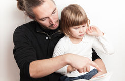 Young man reading book with little Caucasian girl. Young men reading book with little Caucasian girl, studio shoot Royalty Free Stock Photography