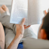 Young man reading book while lying on the couch Stock Image
