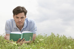 Young man reading book while lying on grass against sky Royalty Free Stock Images
