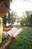 Young man reading a book lying on grass Stock Photo