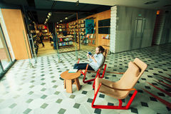 Young man reading a book near bookstore inside modern art gallery Royalty Free Stock Photography