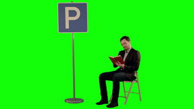 Young man reading a book near parking sign on a. Green Screen, Chroma Key. Professional shot on BMCC RAW with high dynamic range. You can use it e.g in your stock footage