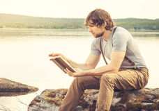 Young Man reading book outdoor. With lake on background Summer vacations and Lifestyle concept Stock Photography