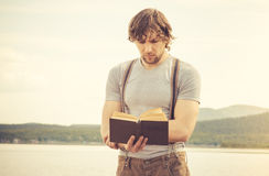 Young Man reading book outdoor Royalty Free Stock Photography
