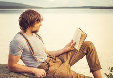 Young Man reading book outdoor. With lake on background Summer vacations and Lifestyle concept Stock Photo