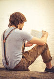 Young Man reading book outdoor. With lake on background Summer vacations and Lifestyle concept Stock Image