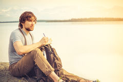 Young Man reading book outdoor. With lake on background Summer vacations and Lifestyle concept Royalty Free Stock Images