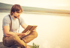 Young Man reading book outdoor Stock Photo