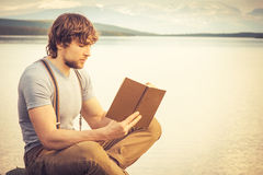 Young Man reading book outdoor. With lake on background Summer vacations and Lifestyle concept Royalty Free Stock Image