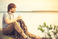 Young Man reading book outdoor. With lake on background Summer vacations and Lifestyle concept Royalty Free Stock Photography