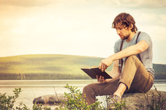 Young Man reading book outdoor Lifestyle. Young Man reading book outdoor with lake on background Summer vacations and Lifestyle concept Royalty Free Stock Photo