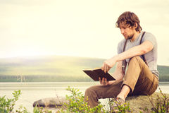 Young Man reading book outdoor with scandinavian lake on background. Education and Lifestyle Travel concept Royalty Free Stock Image