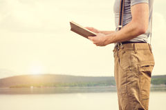 Young Man reading book outdoor with scandinavian lake on background. Education and Lifestyle Travel concept Stock Photo