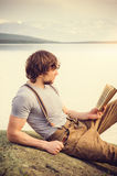 Young Man reading book outdoor with scandinavian lake on background Stock Photography