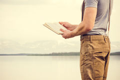 Young Man reading book outdoor with scandinavian lake on background. Education and Lifestyle Travel concept Stock Photos