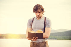Young Man reading book outdoor with scandinavian lake on background. Education and Lifestyle Travel concept Stock Image