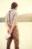 Young Man reading book outdoor with scandinavian lake on background. Education and Lifestyle Travel concept Stock Photography