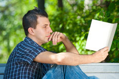 Young man reading book outdoors. Handsome young man sitting on the bench and reading book outdoors royalty free stock photography