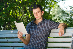 Young man reading book outdoors Royalty Free Stock Photo