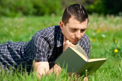 Young man reading book outdoors Stock Photography