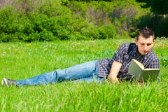Young man reading book outdoors Stock Photo