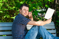 Young man reading book outdoors Stock Image