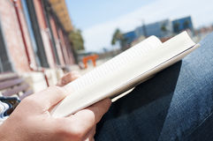 Young man reading a book outdoors Stock Image