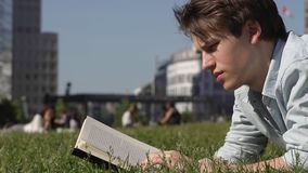 Young Man Reading A Book Outdoors. Young Male Lays On The Grass Reading A Book In Slow Motion. Urban Background With Buildings And People On A Sunny Summer Day stock footage