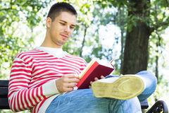 Young man reading a book. In the park Stock Photos