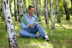 Young man reading book in park Royalty Free Stock Image